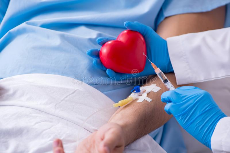 得到在医院诊所的男性患者输血 免版税库存图片