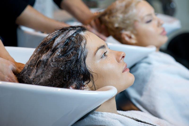 得到在发廊的美丽的妇女一次头发洗涤 库存照片