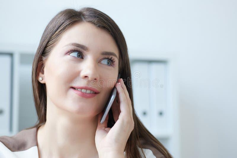 得到在手机的成功的女商人好消息 移动电话微笑的联系的妇女 企业概念查出的成功白色 库存图片