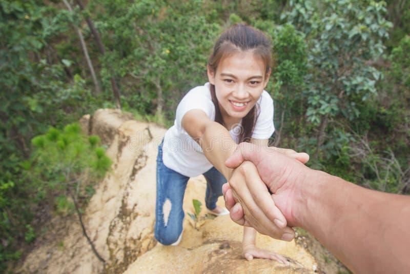 得到在远足微笑的愉快的ov的帮助的手远足者妇女帮助 免版税库存图片