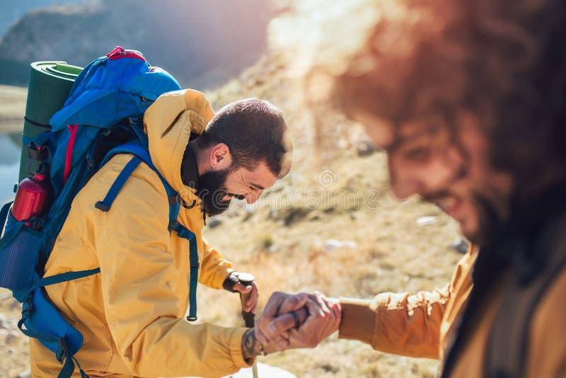 得到在远足愉快的克服的障碍的徒步旅行者人帮助 库存图片
