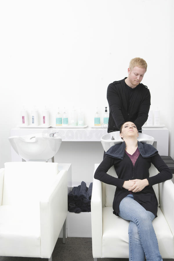 得到她在沙龙的妇女头发洗涤 免版税库存照片