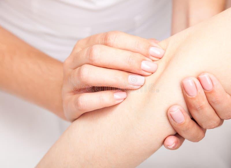 得到她的手肘的整骨疗法治疗的妇女 免版税库存照片