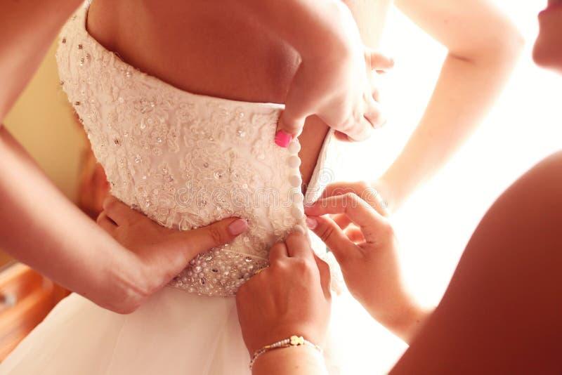 得到她的礼服的女傧相帮助的新娘  免版税库存照片