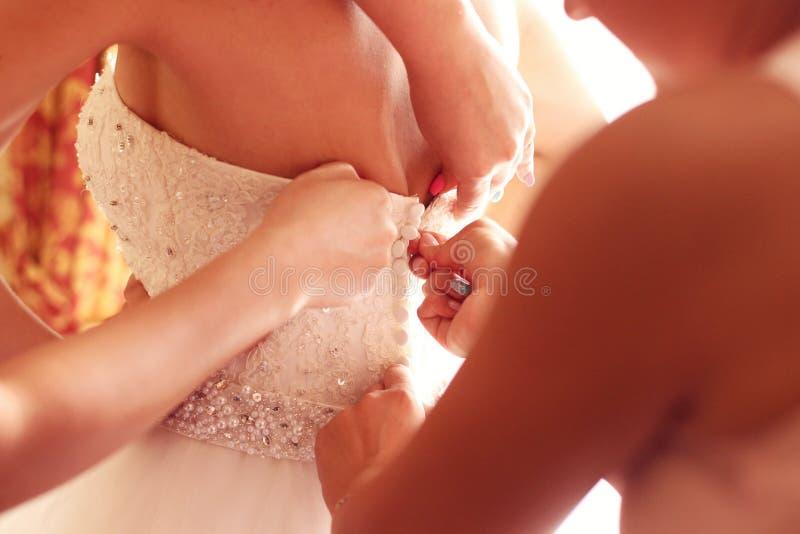 得到她的礼服的女傧相帮助的新娘  库存照片