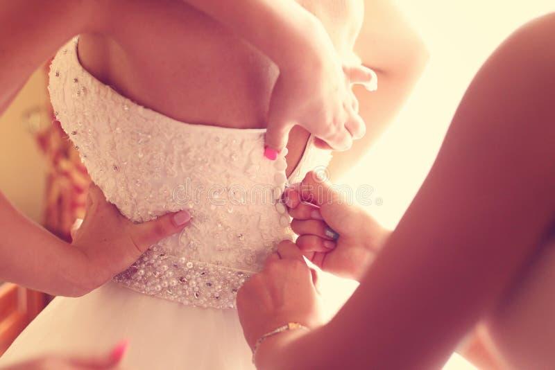 得到她的礼服的女傧相帮助的新娘  库存图片