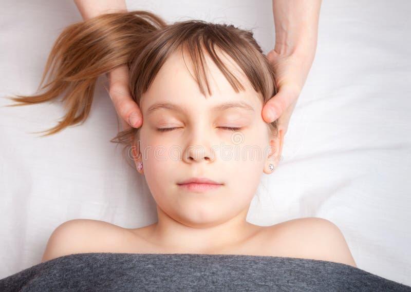 得到她的头的整骨疗法治疗的女孩 免版税库存照片