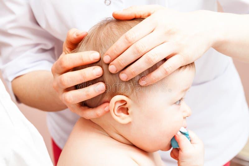 得到她的头的整骨疗法治疗的婴儿 免版税库存图片