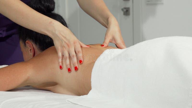 得到安慰性的按摩的妇女由于一个专业女按摩师的作用 库存照片