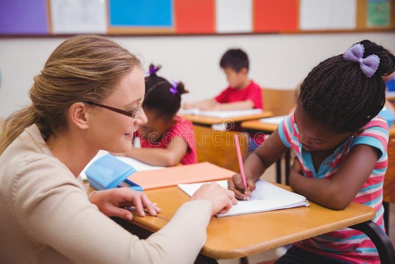 得到帮助的逗人喜爱的学生从老师在教室 库存图片