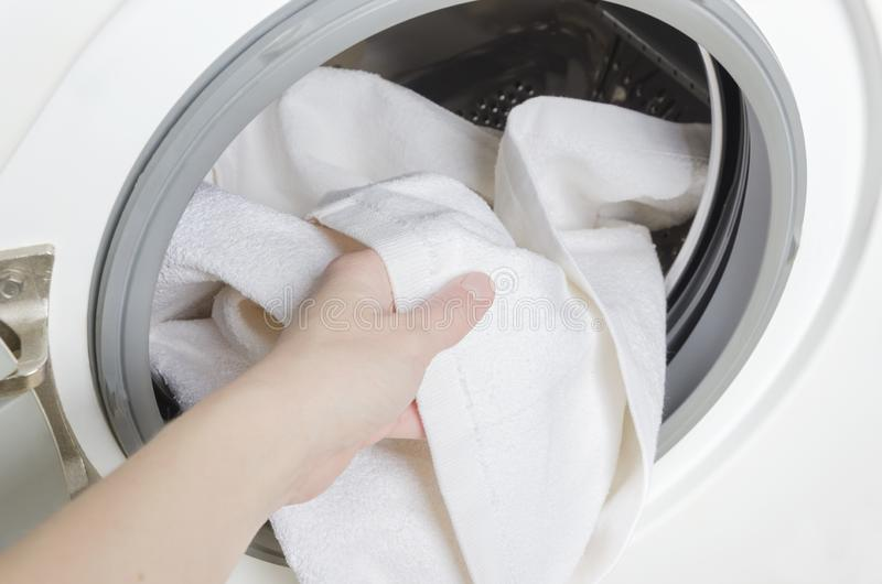 得到干净的白色毛巾的妇女在洗涤以后 有衣裳的洗衣机 图库摄影