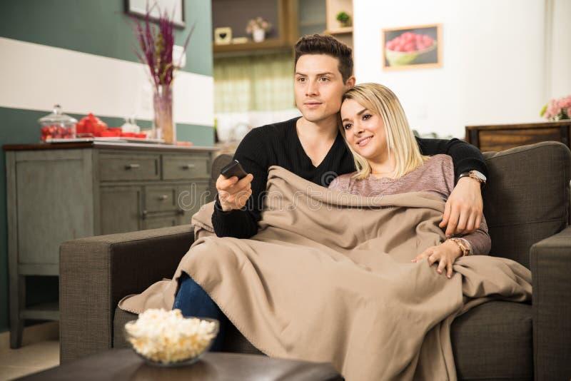得到所有舒适和观看的电视的夫妇 库存图片