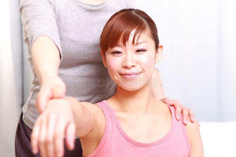 得到按摩脊柱治疗者的年轻日本妇女 库存照片