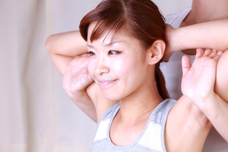 得到按摩脊柱治疗者的年轻日本妇女 免版税库存照片