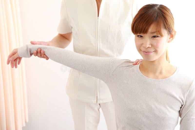 得到按摩脊柱治疗者的年轻日本妇女 免版税图库摄影