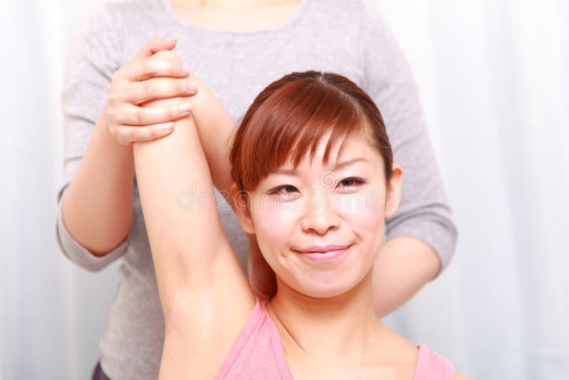 得到按摩脊柱治疗者的年轻日本妇女 库存图片