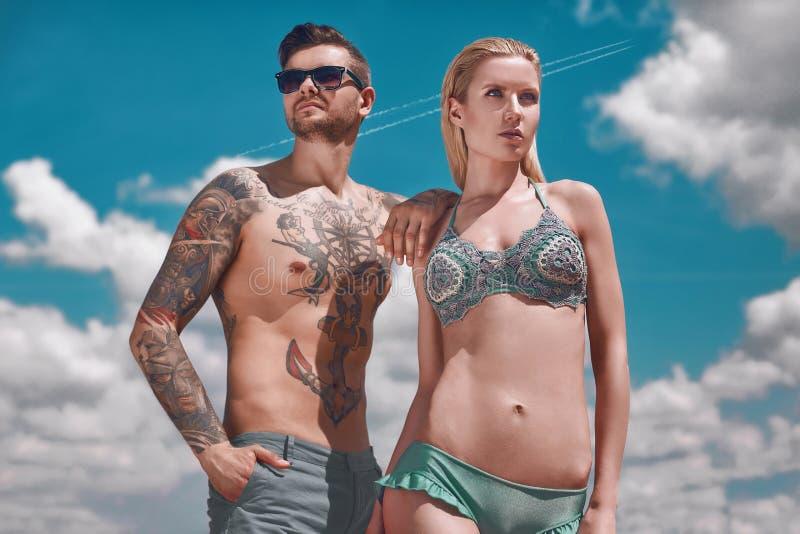 得到晒黑的时尚美好的夫妇 免版税图库摄影