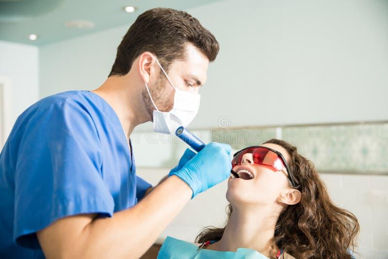 得到治疗的妇女从诊所的牙医 免版税库存图片