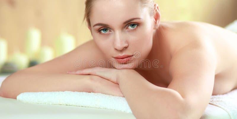 得到温泉按摩的美丽的少妇,说谎在沙龙 免版税库存图片