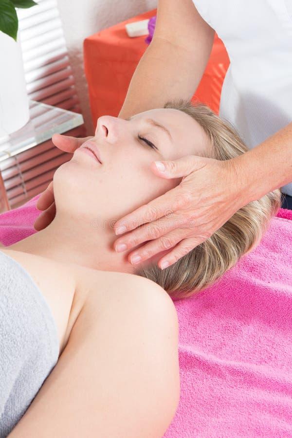 得到温泉治疗的白肤金发的妇女在美容院面孔按摩面部秀丽治疗 库存照片