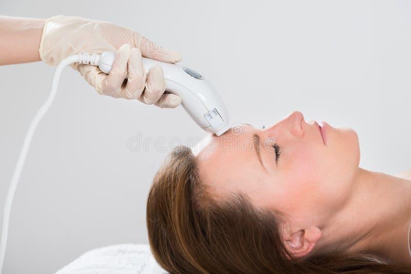得到激光头发撤除治疗的妇女 库存照片