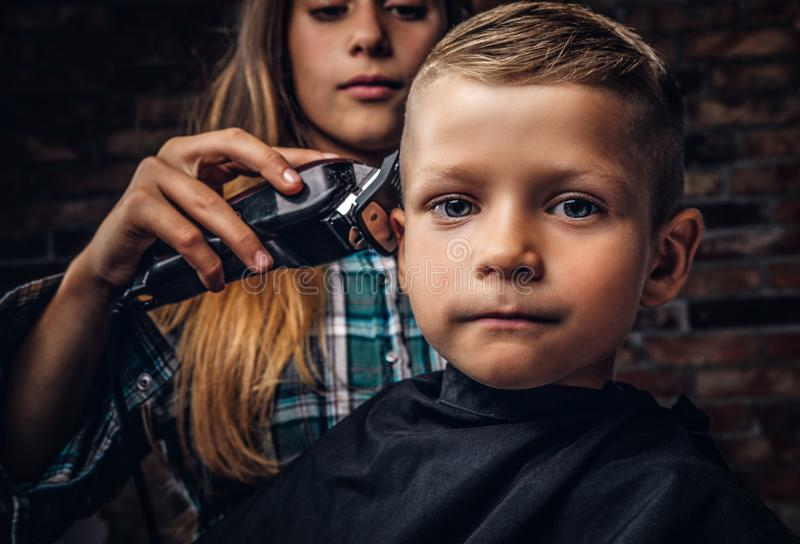 得到理发的一个逗人喜爱的学龄前儿童男孩的特写镜头画象 更老的姐妹切开她的有整理者的弟弟 图库摄影