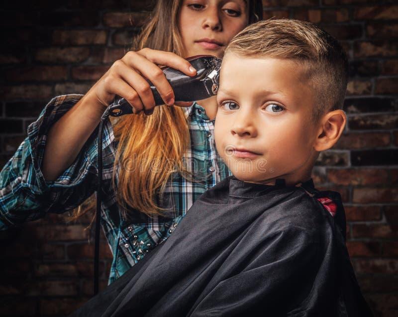 得到理发的一个逗人喜爱的学龄前儿童男孩的特写镜头画象 更老的姐妹切开她的有整理者的弟弟 免版税库存照片