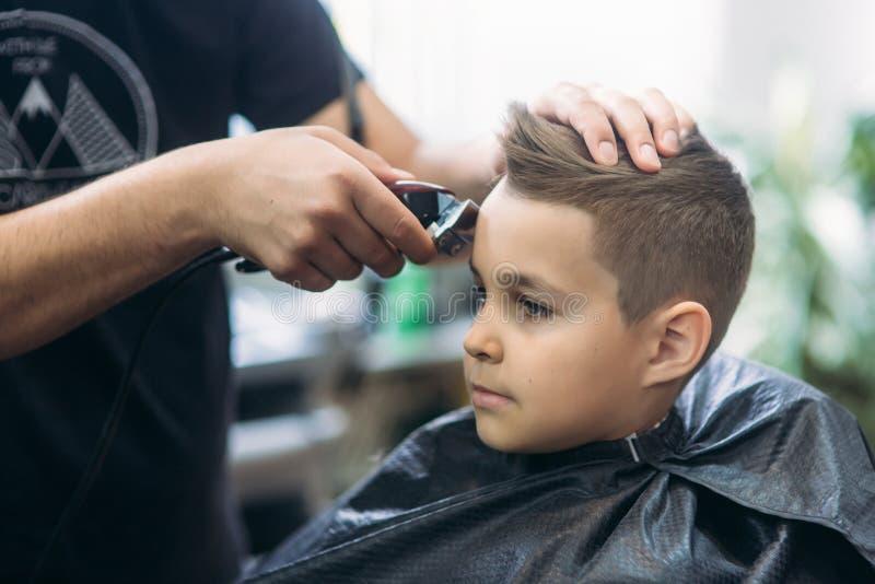 得到理发的小男孩由理发师,当坐在椅子在理发店时  免版税库存照片