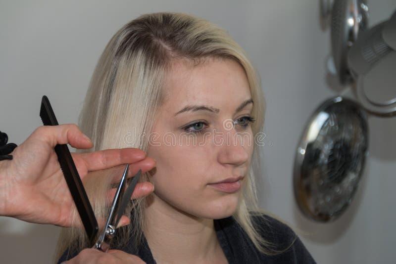 得到理发的美丽的白肤金发的女孩 免版税库存图片