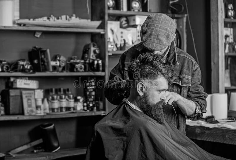得到理发的行家客户 有头发剪刀工作的理发师在有胡子的人理发店背景理发  ?? 免版税库存图片