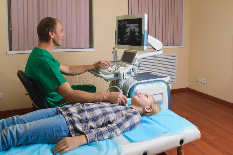 得到甲状腺的超声波的女孩从医生 库存图片