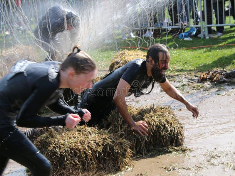 得到的妇女和人战斗通过泥,喷与wat 图库摄影