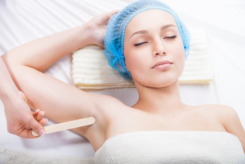 得到的妇女给腋窝打蜡由美容师 库存图片