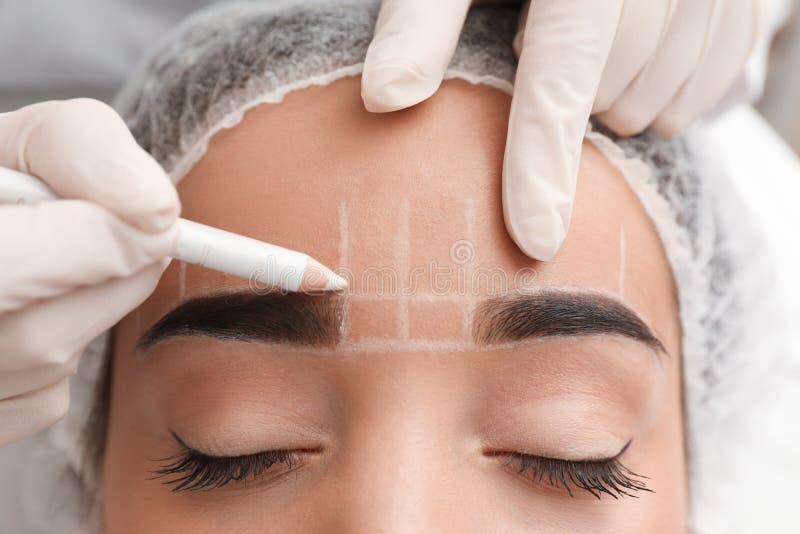 得到的年轻女人为永久眼眉构成做准备做法在纹身花刺沙龙的 免版税库存图片