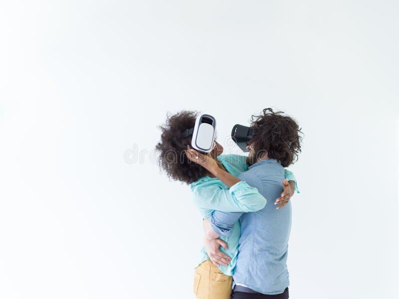 得到经验的不同种族的夫妇使用VR耳机玻璃 免版税图库摄影