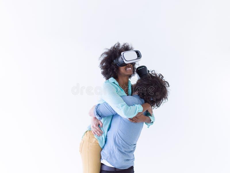 得到经验的不同种族的夫妇使用VR耳机玻璃 免版税库存图片