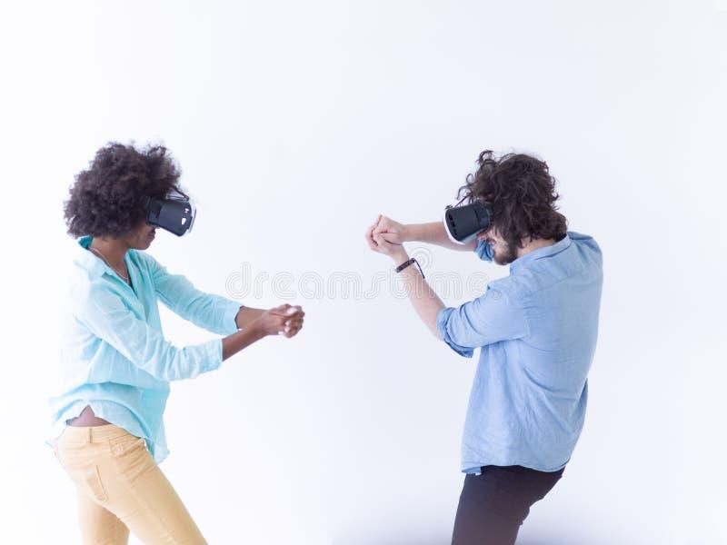 得到经验的不同种族的夫妇使用VR耳机玻璃 免版税库存照片