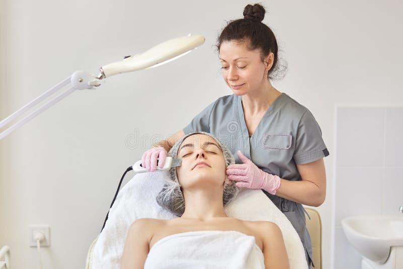 得到超音波脸面护理的可爱的年轻女人的图象洗涤,做超声波面孔清洁的专业美容师 免版税图库摄影