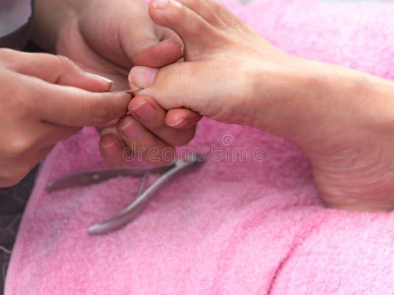 得到趾甲修脚服务的妇女由专业pedicurist在钉子沙龙 美容师文件在钉子和温泉的钉子修脚 库存照片