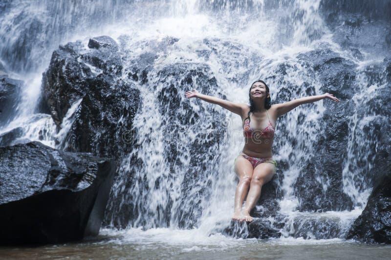 得到身体自然惊人的瀑布的湿下面小河比基尼泳装的年轻美丽和甜亚裔妇女坐岩石感觉 免版税库存照片