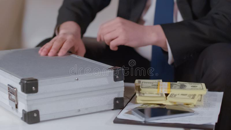 得到金钱的企业家从公文包,秘密生意的佣金 免版税库存照片