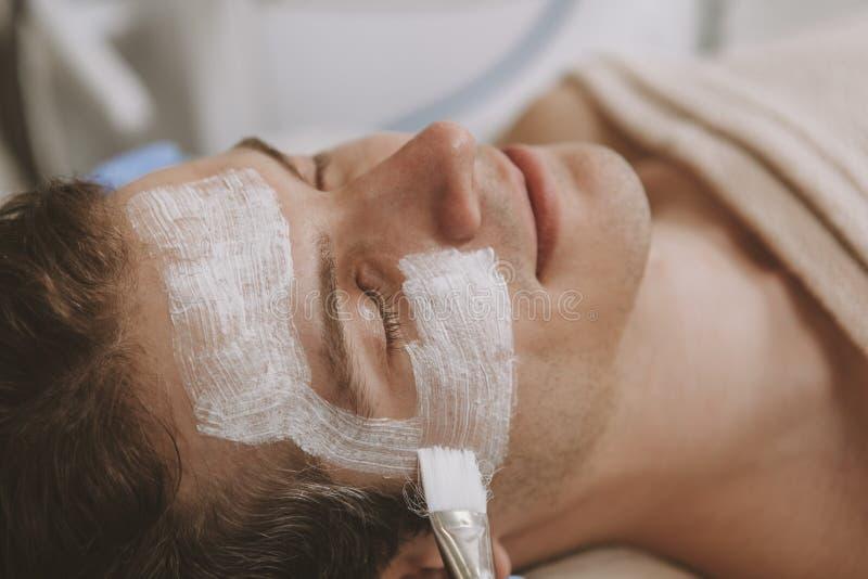 得到面部skincare治疗的帅哥 免版税库存照片