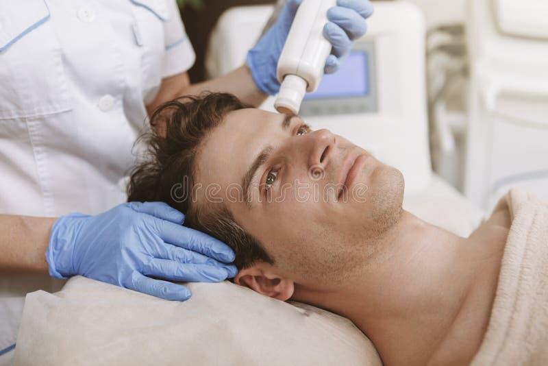 得到面部skincare治疗的帅哥 免版税库存图片