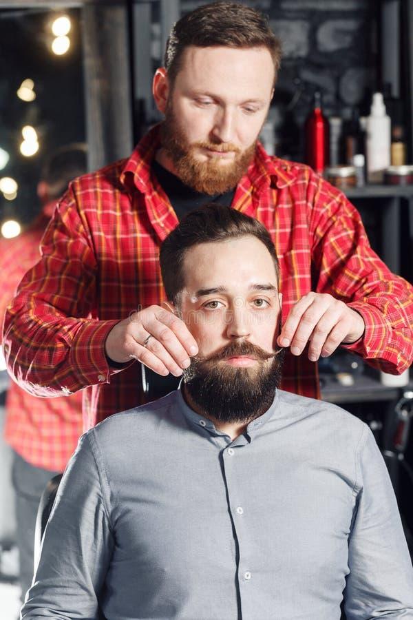 得到他的髭的行家人准备好在理发店的转弯胡子 免版税库存图片