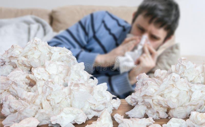 得流感或寒冷的滑稽的病的人吹他的鼻子 免版税库存照片