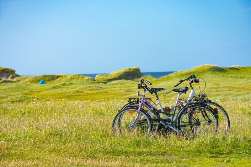 循环和wildcamping -在绿色machair的两辆自行车在背景中调遣,与一个帐篷 图库摄影