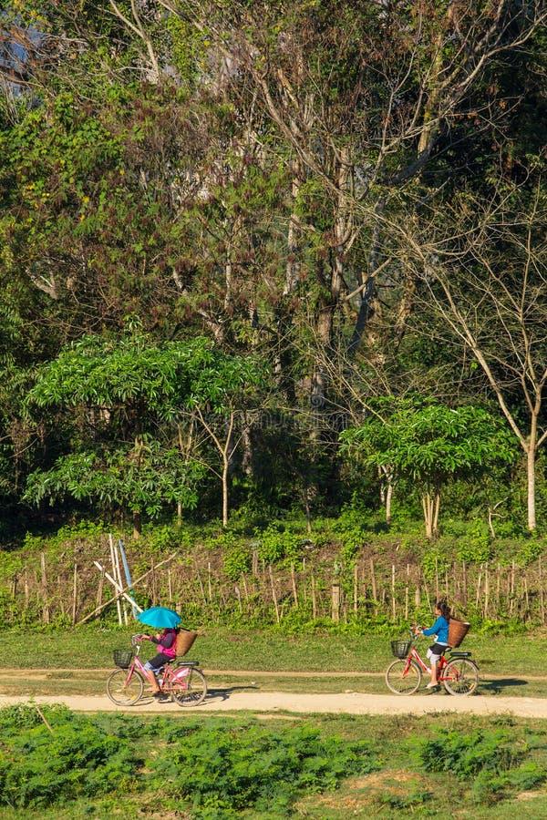循环在一条农村路的不明身份的女孩在Vang Vieng村庄,老挝 免版税库存图片