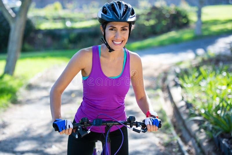 循环在乡下的女性骑自行车者在晴天 免版税库存照片