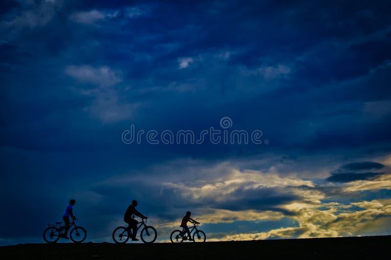 循环在健康的公园的剪影在日落背景 免版税库存照片