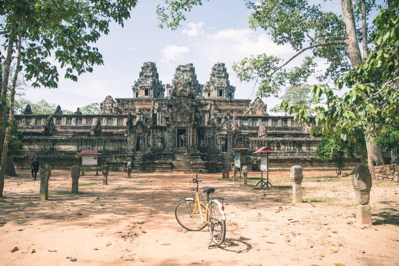 循环在吴哥寺庙,柬埔寨附近的旅游夫妇 茶胶寺大厦废墟在密林 Eco友好旅游业旅行 免版税图库摄影